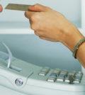 Cashier Handing Credit Card to Customer ca. 2002